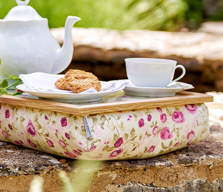 Bean Bag lap tray in Mulberry Rose on a wall in a garden with a tea set and biscuit on top
