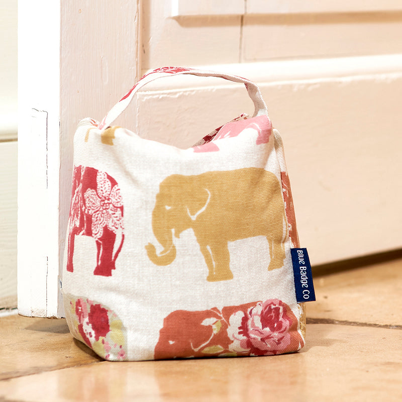 Fabric Door Stop in Nelly Elephant with blue badge company label showing, holding an open white door