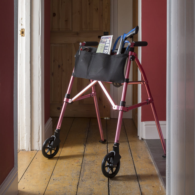 Pink foldable walking frame opened and in use in hallway at home