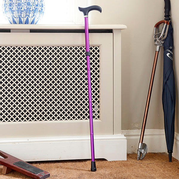 Adjustable Folding Walking Stick Cane in Purple is fully extended leant against wall at home with umbrella beside