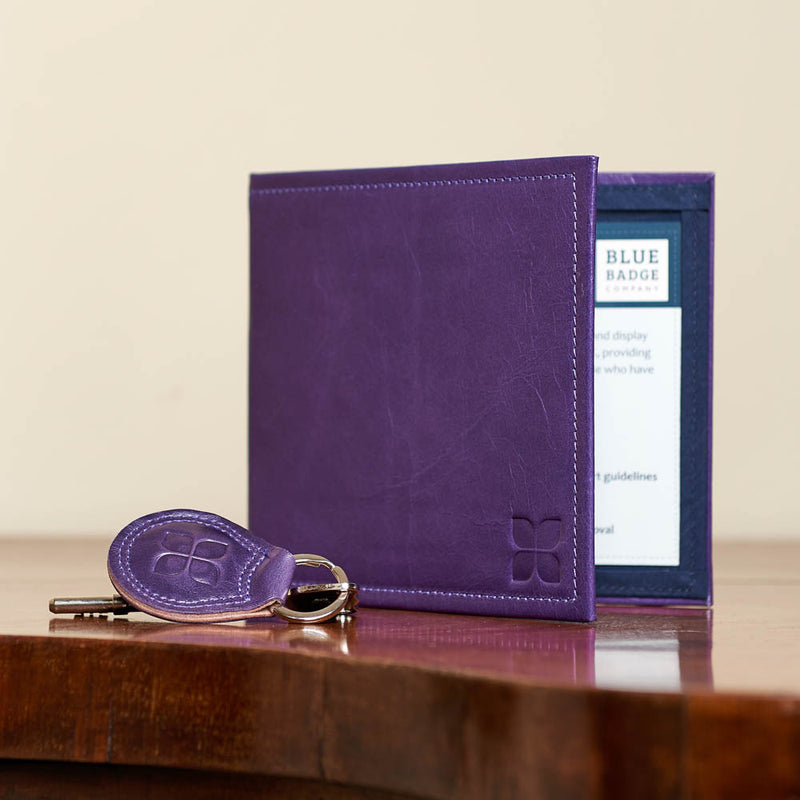 Leather Blue Badge Wallet, Keyring and RADAR Disabled Toilet Key in Purple with blue badge company logo embossed on both items on an oak table at home