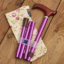 Adjustable Folding Walking Stick in Purple & Fabric Storage Bag in Mulberry Rose with blue badge company label showing on wooden floor