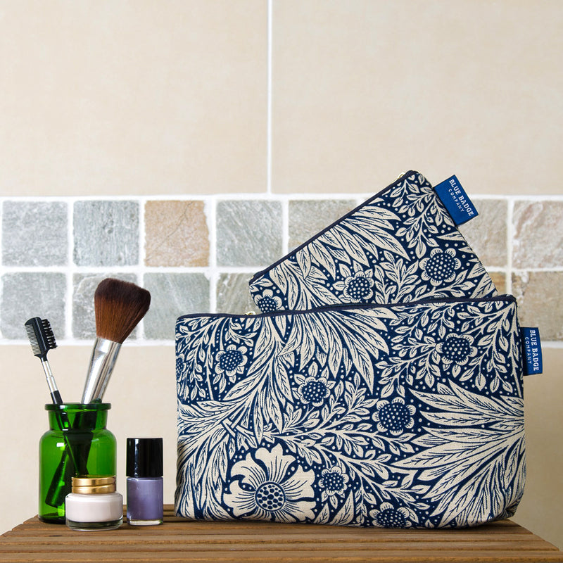 Wash Bag & Make-up Purse Gift Set in William Morris Marigold Indigo with blue badge company label showing and placed on bathroom shelf