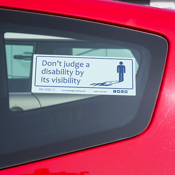 Disabled Car Sticker Rectangle  - Don't judge a disability by it's visibility is stuck on the inside of a red car