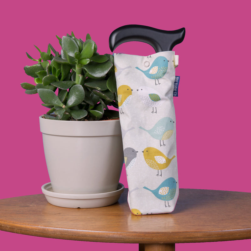 Garden Birds Storage Bag and Purple folding Walking Stick on a table