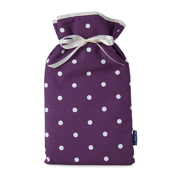 Large Hot Water Bottle with soft cover in Purple Spotty with white satin ribbon and blue badge company label showing