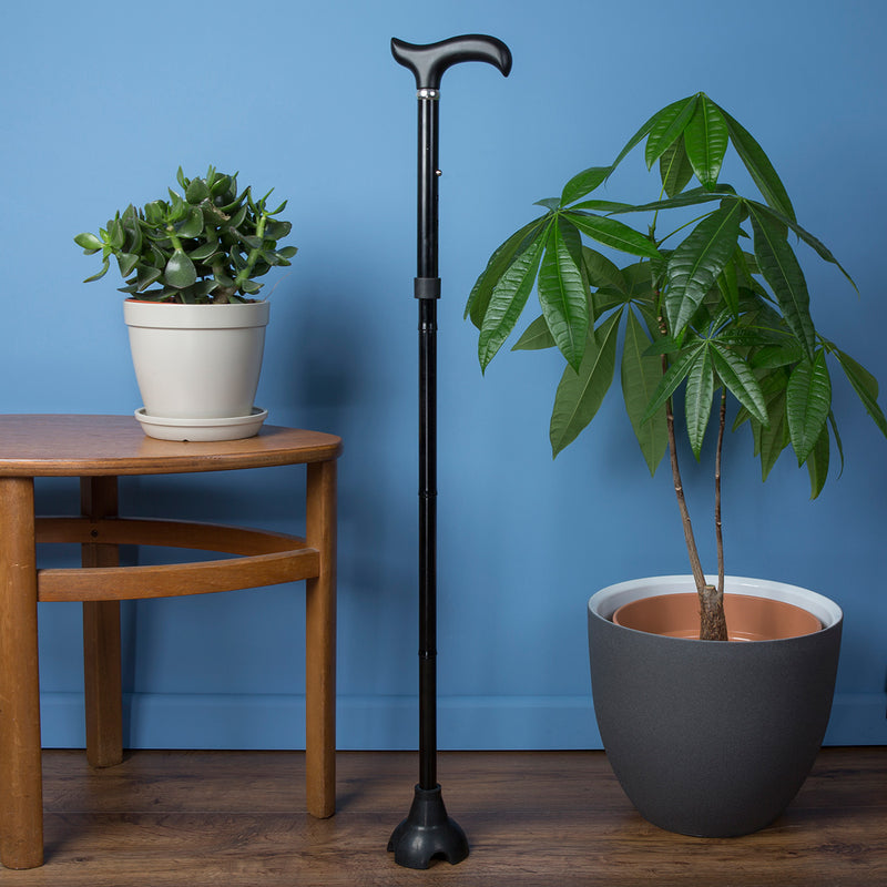 Freestanding Adjustable Folding Walking Stick Cane in Black fully extended and placed in living room next to plant and coffee table