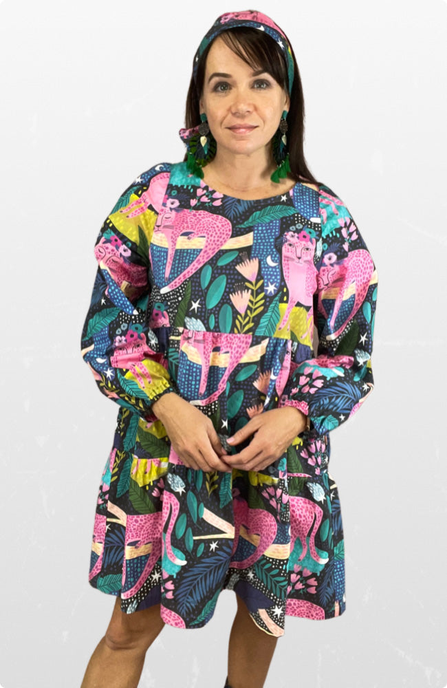 Woman wearing a knee length long sleeved dress with a bold print of pink jungle cats and colours of teal, mustard and green.