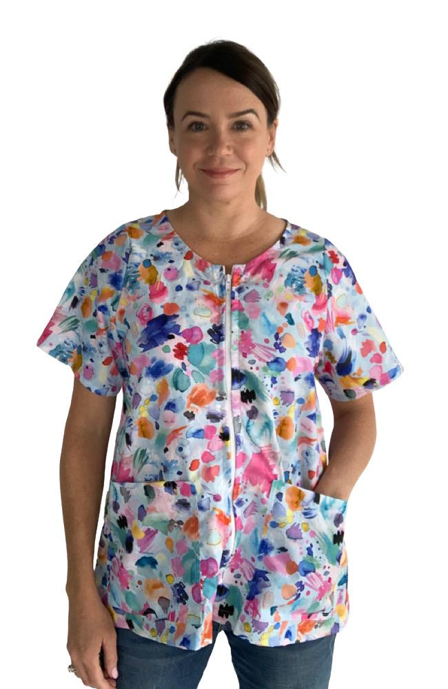 Woman in a bright patterned short sleeve scrub top with a zip front and a paint splatter design