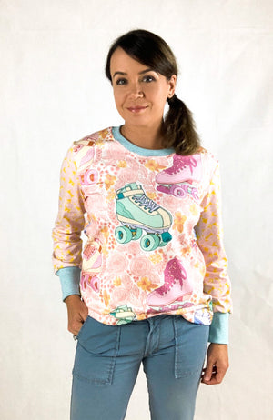 Women wearing a long sleeve t-shirt with a print in pale pink floral with large rollerskates in blue and purple. The sleeves of the tshirt are in a contrast fabric with tiny pink leaves.