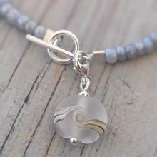 Load image into Gallery viewer, white frosted clip on charm round flat with ivory wave and seed bead bracelet
