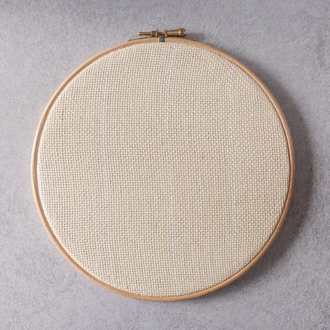Fabric stretched in an embroidery hoop for punch needle