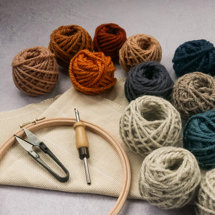 Punch needle, thread snips, monks cloth fabric, hoop and balls of yarn