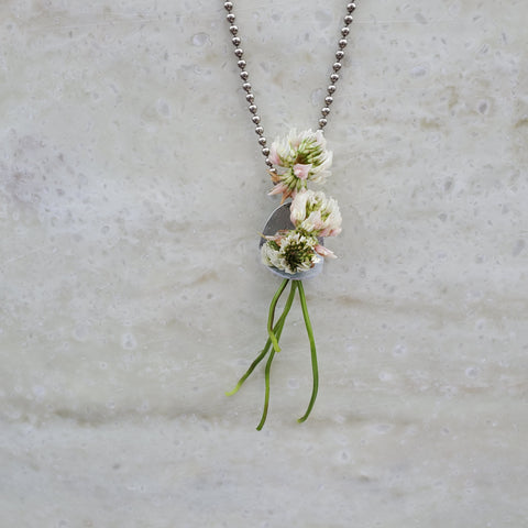 clover flowers in flower holder pendant