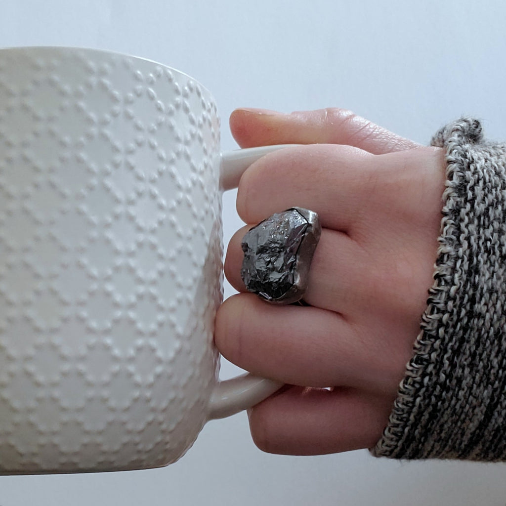 crystalline silicon ring on hand with white mug