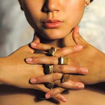 Miya modeling big brass rings on 5 fingers