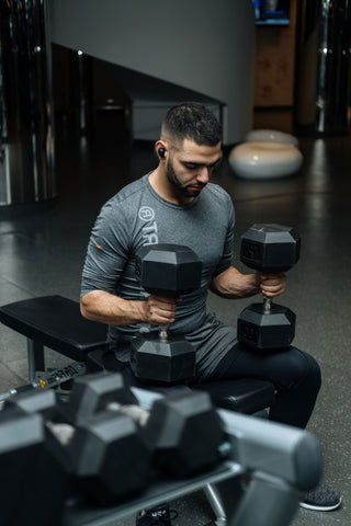 man holding two dumbbells sitting on a bench