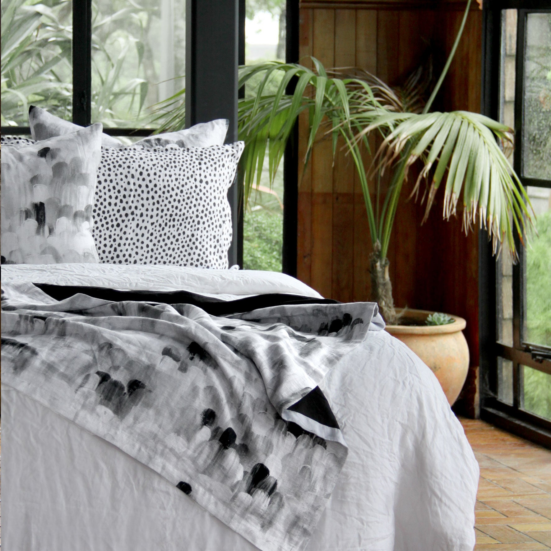 Linen throw blanket on the end of a bed. Linen bed linen in tones of white, grey and black