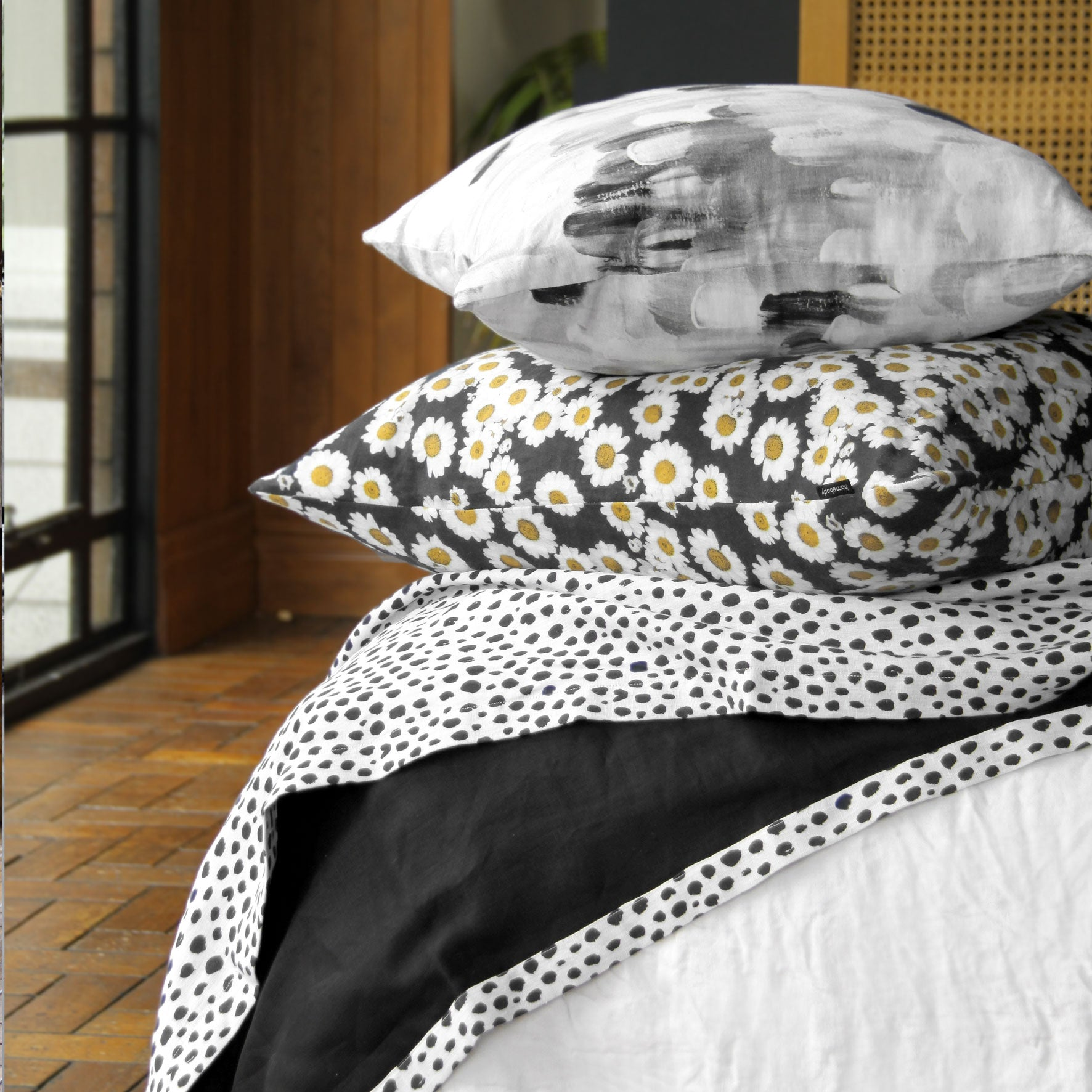 two cushions and a linen throw blanket on a bed. black and white animal print