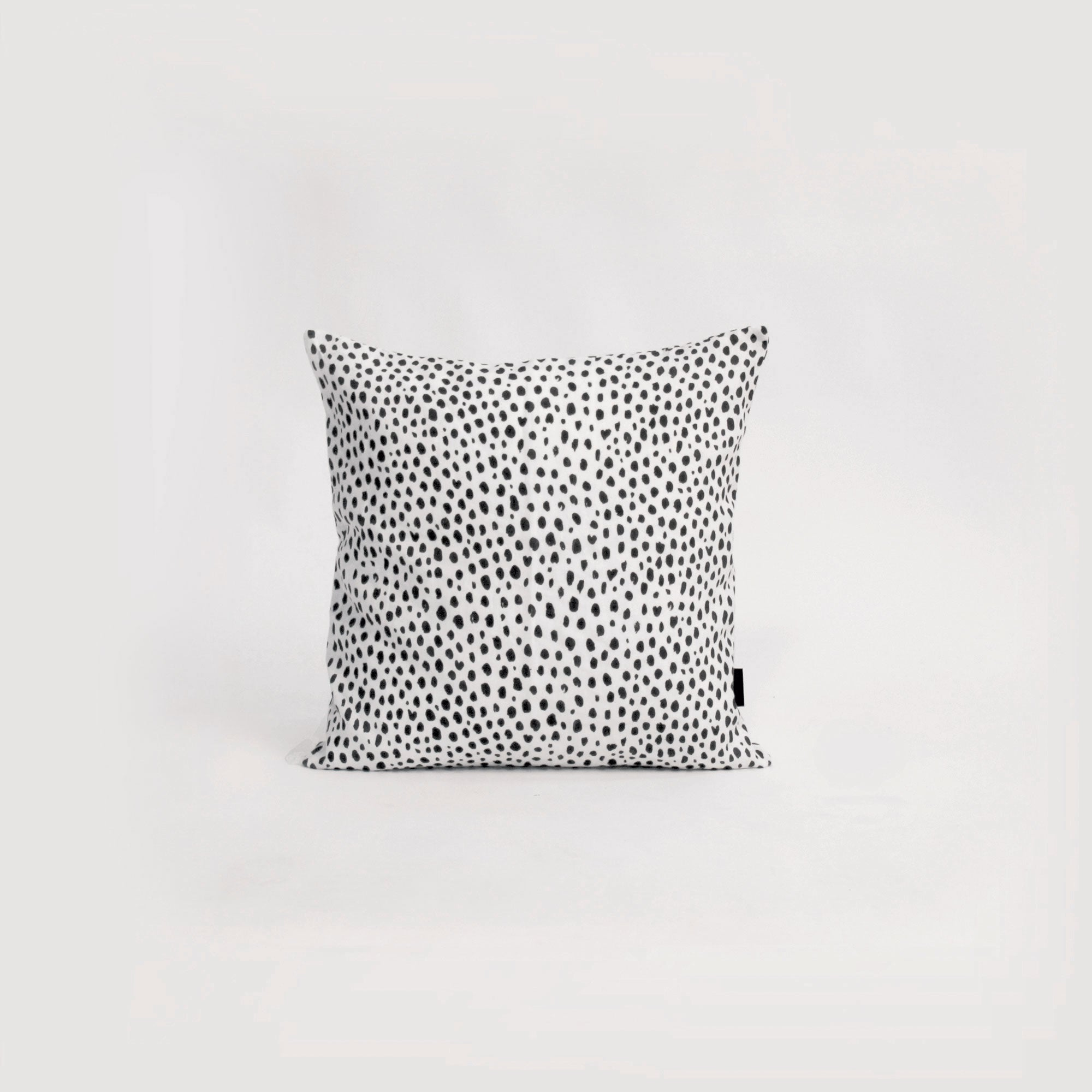 animal print cushion with black and white spots. Natural linen