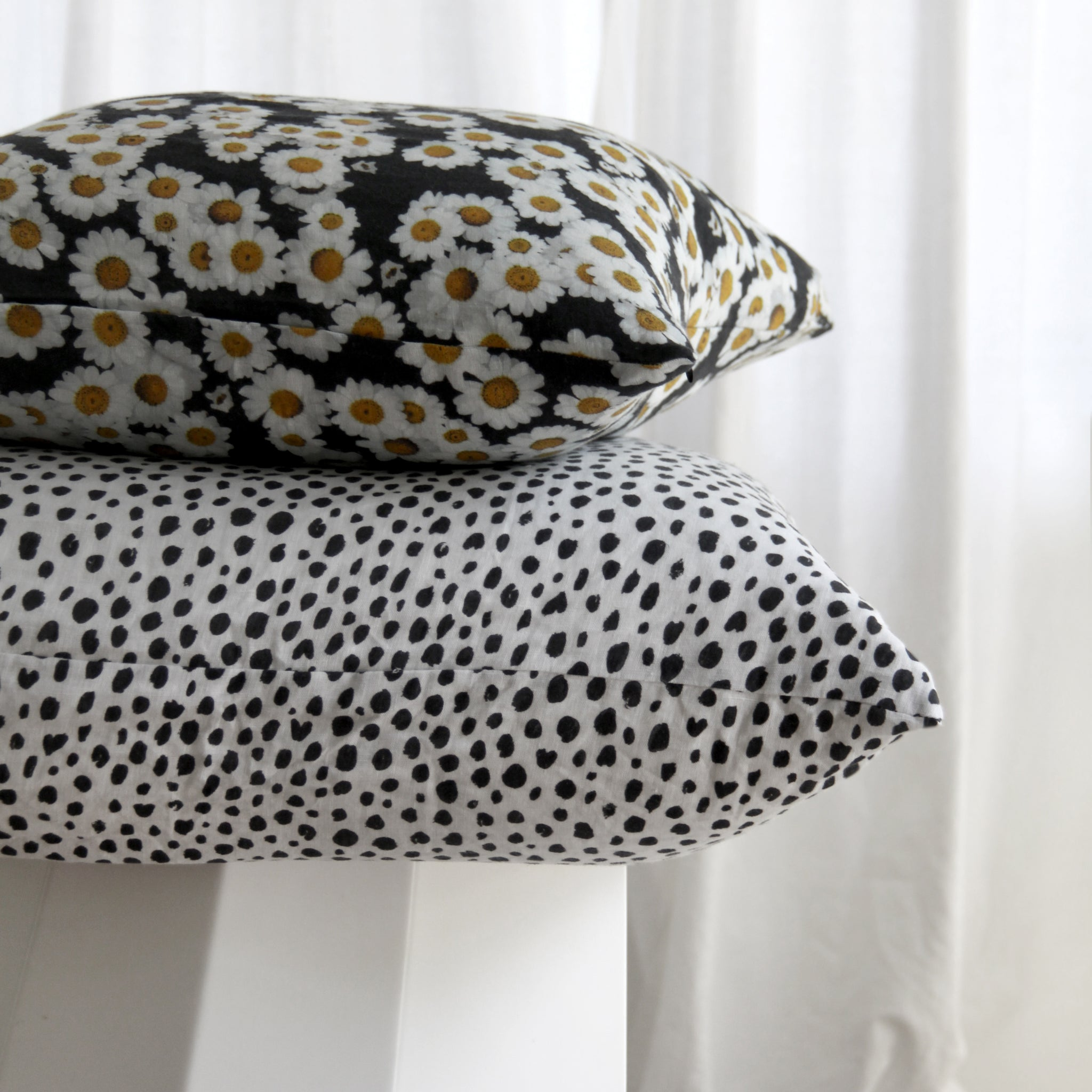 homebody printed linen stack of cushions with daisy and animal print design