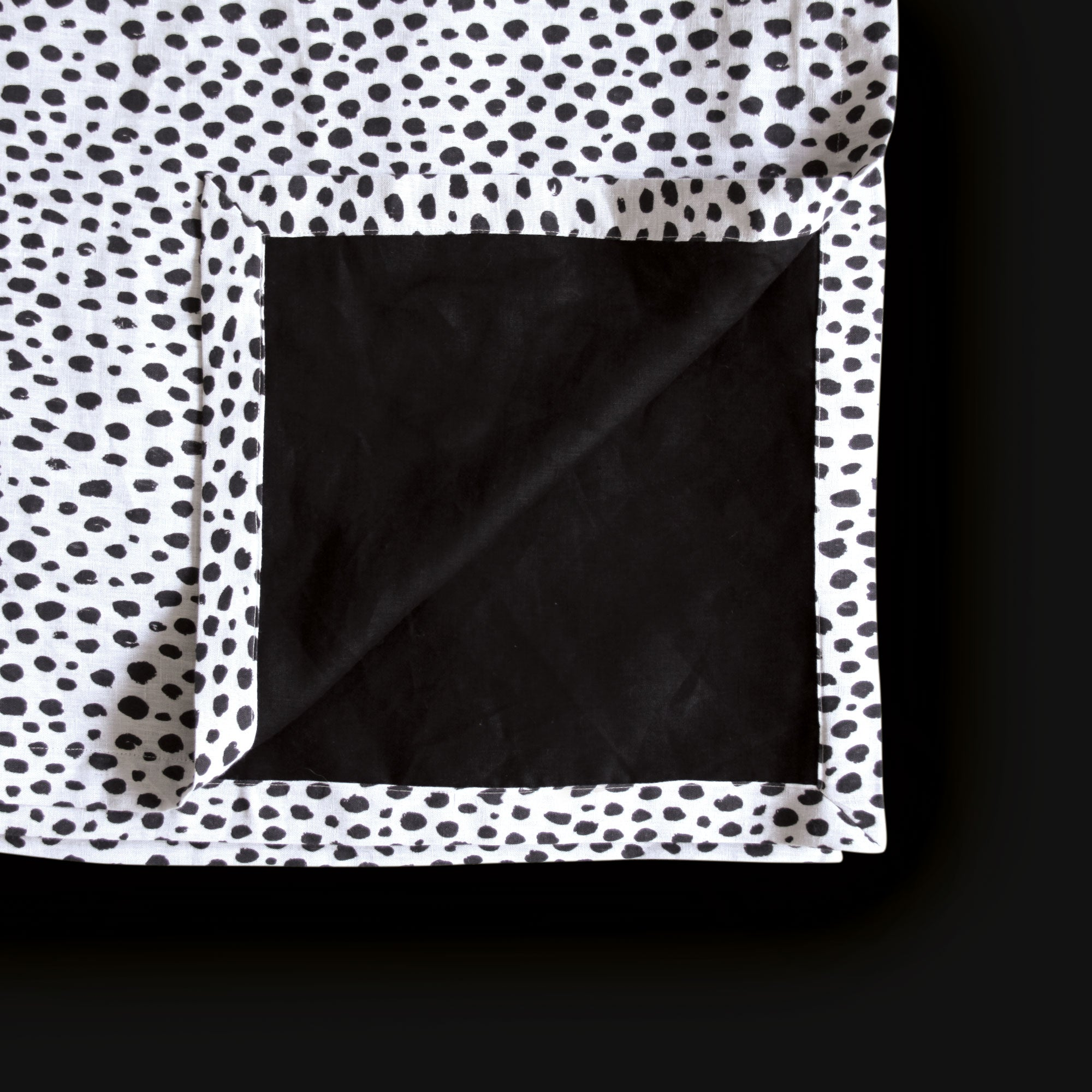 Black and white linen throw blanket showing animal print on one side and plain black linen on the other