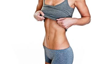 athletic woman lifting up tank top to show off toned abdominal muscles