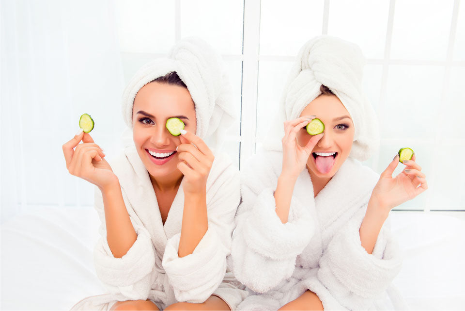 Two friends laugh and have fun in robes at spa
