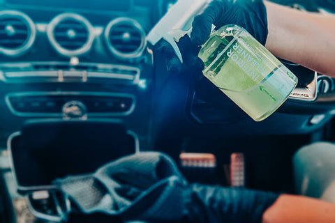 Bottle of Green 500ml Interior Cleaner being sprayed held by gloved hands and being sprayed on a BMW interior