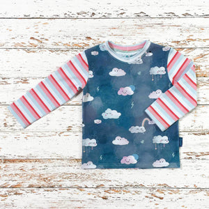 Sugar and Storm's Long Sleeve Tee made from beautifully soft organic cotton jersey. GOTS and EOKO-TEX certified. This pattern is called Head in The Clouds with Sugar Stripe. The pattern contains clouds with cute faces against a textured blue sky. The clouds have a variety of expressions and there are also small details such as hearts and lightening. The sleeves and neck band are the Sugar Stripe pattern.