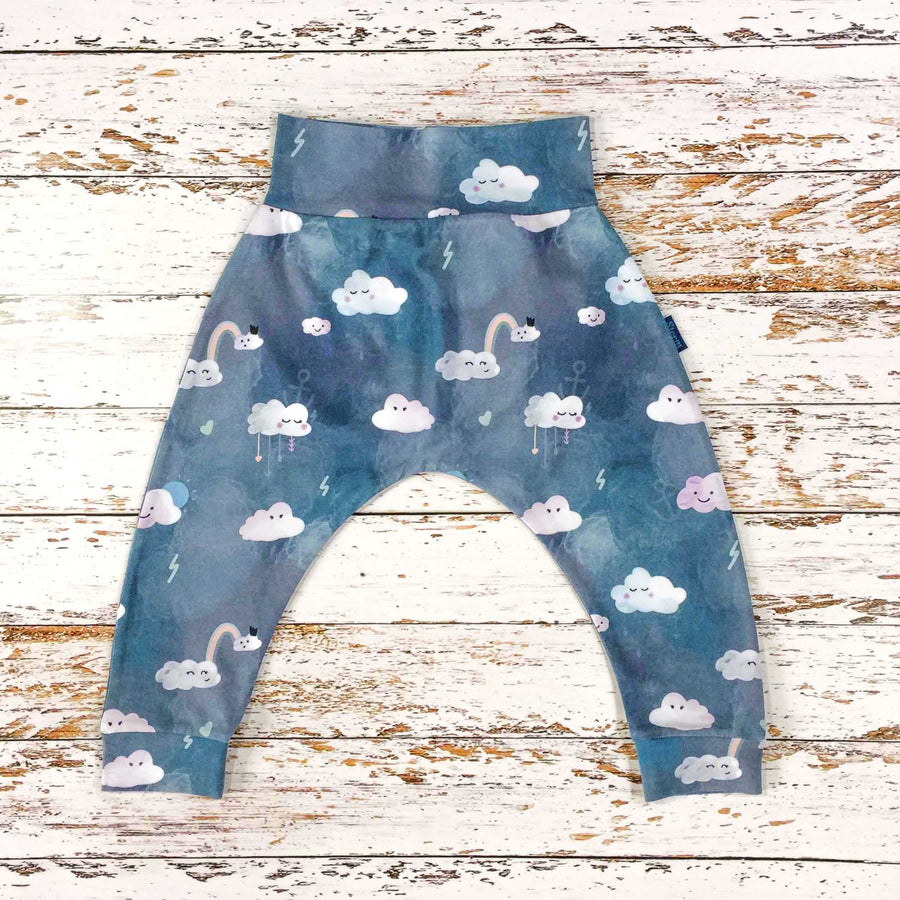 Sugar and Storm's Harem Pants made from beautifully soft organic cotton jersey. GOTS and EOKO-TEX certified. This pattern is called Head in The Clouds. The pattern contains clouds with cute faces against a textured blue sky. The clouds have a variety of expressions and there are also small details such as hearts and lightening.