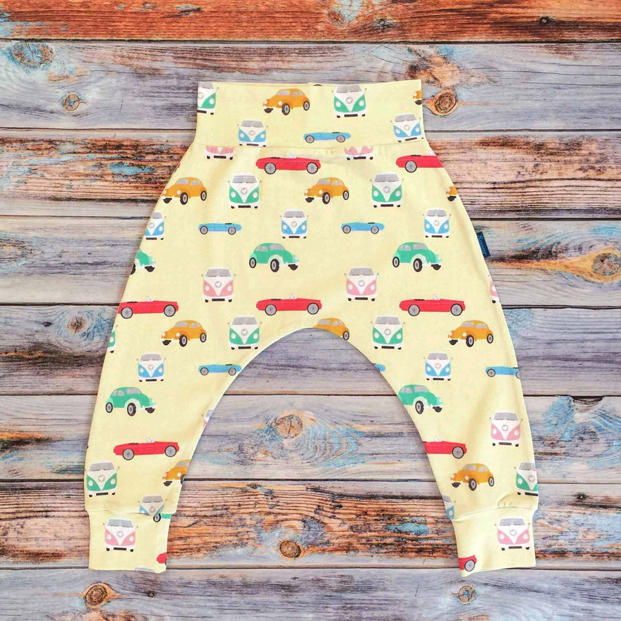 Sugar and Storm's Harem Pants made from beautifully soft organic cotton jersey. GOTS and EOKO-TEX certified. This retro pattern is called Memory Lane. The patter contains a variety of vintage cars and camper vans of different candy colours on a pale-yellow background.