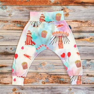 Sugar and Storm's Harem Pants made from beautifully soft organic cotton jersey. GOTS and EOKO-TEX certified. This pattern is called Sugar Rush! The pattern contains a scene of a carnival at dusk with textured bright reds and pinks, and a splash of blue. A helter skelter, ferris wheel and hearts and balloons can be seen amongst popcorn and bright lights.