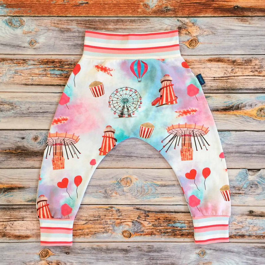 Sugar and Storm's Harem Pants made from beautifully soft organic cotton jersey. GOTS and EOKO-TEX certified. This pattern is called Sugar Rush! With Sugar Stripe. The pattern contains a scene of a carnival at dusk with textured bright reds and pinks, and a splash of blue. A helter skelter, ferris wheel and hearts and balloons can be seen amongst popcorn and bright lights. The sleeves and neck band are the Sugar Stripe pattern.