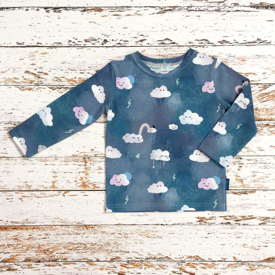 Sugar and Storm's Long Sleeve Tee made from beautifully soft organic cotton jersey. GOTS and EOKO-TEX certified. This pattern is called Head in The Clouds. The pattern contains clouds with cute faces against a textured blue sky. The clouds have a variety of expressions and there are also small details such as hearts and lightening.