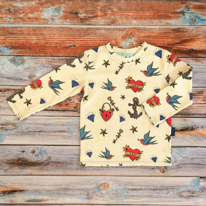 Sugar and Storm's Long Sleeve Tee made from beautifully soft organic cotton jersey. GOTS and EOKO-TEX certified. This pattern is called Hold Fast. The pattern contains images of child friendly traditional sailor tattoos such as hearts, swallows, anchors, and a nautical star against a pale-yellow background.