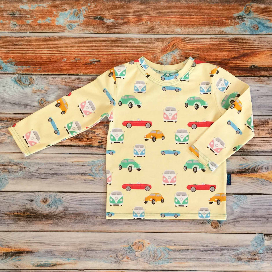 Sugar and Storm's Long Sleeve Tee made from beautifully soft organic cotton jersey. GOTS and EOKO-TEX certified. This retro pattern is called Memory Lane. The patter contains a variety of vintage cars and camper vans of different candy colours on a pale-yellow background.