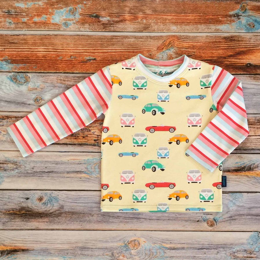 Sugar and Storm's Long Sleeve Tee made from beautifully soft organic cotton jersey. GOTS and EOKO-TEX certified. This retro pattern is called Memory Lane with Sugar Stripe. The patter contains a variety of vintage cars and camper vans of different candy colours on a pale-yellow background. The sleeves and neck band are the Sugar Stripe pattern.