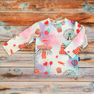 Sugar rush Sugar and Storm's Long Sleeve Tee made from beautifully soft organic cotton jersey. GOTS and EOKO-TEX certified. This pattern is called Sugar Rush! The pattern contains a scene of a carnival at dusk with textured bright reds and pinks, and a splash of blue. A helter skelter, ferris wheel and hearts and balloons can be seen amongst popcorn and bright lights.