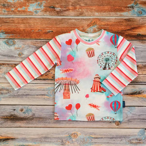 Sugar and Storm's Long Sleeve Tee made from beautifully soft organic cotton jersey. GOTS and EOKO-TEX certified. This pattern is called Sugar Rush! With Sugar Stripe. The pattern contains a scene of a carnival at dusk with textured bright reds and pinks, and a splash of blue. A helter skelter, ferris wheel and hearts and balloons can be seen amongst popcorn and bright lights. The sleeves and neck band are the Sugar Stripe pattern.