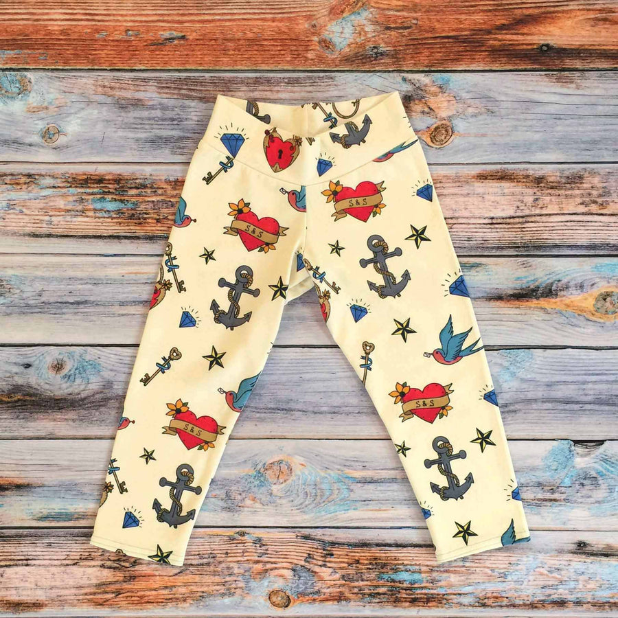 Sugar and Storm's relaxed fit Leggings made from beautifully soft organic cotton jersey. GOTS and EOKO-TEX certified. This pattern is called Hold Fast. The pattern contains images of child friendly traditional sailor tattoos such as hearts, swallows, anchors, and a nautical star against a pale-yellow background.
