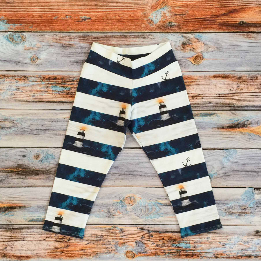 Sugar and Storm's relaxed fit Leggings made from beautifully soft organic cotton jersey. GOTS and EOKO-TEX certified. This pattern is called Shine Through the Storm. The pattern contains Hook lighthouse Wexford, Ireland shining brightly through a stormy sky. The rough seas and pale skies resemble a wide  classical nautical stripe of deep navy blue and grey white.