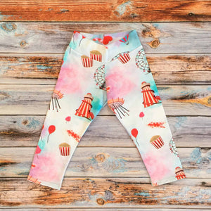 Sugar and Storm's relaxed fit Leggings made from beautifully soft organic cotton jersey. GOTS and EOKO-TEX certified. This pattern is called Sugar Rush! The pattern contains a scene of a carnival at dusk with textured bright reds and pinks, and a splash of blue. A helter skelter, ferris wheel and hearts and balloons can be seen amongst popcorn and bright lights.