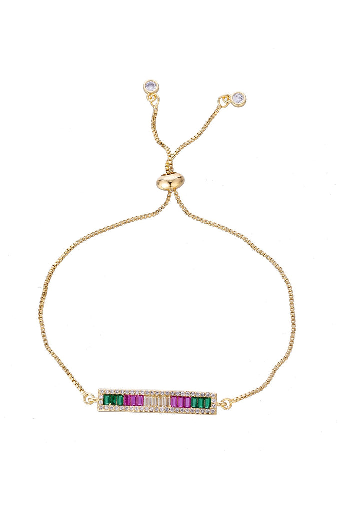 Gold bar bracelet with cubic zirconia setting. Gold bar is linked to gold tone chain. Gold bar features, small pink crystal, small green crystals, small clear crystals. Shown with chain is adjustable with sliding knot.