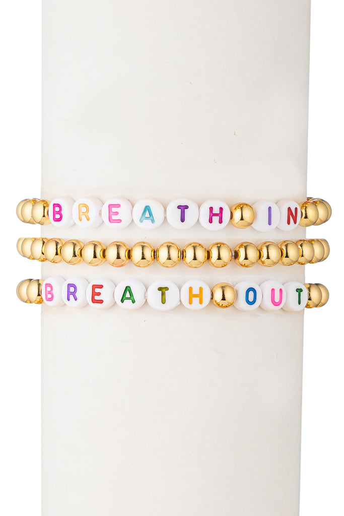 "3 piece gold beaded bracelet set. One bracelet reads ""breathe in"" and one bracelet reads ""breathe out"" with additional gold beads. Third bracelet is fully gold beaded."