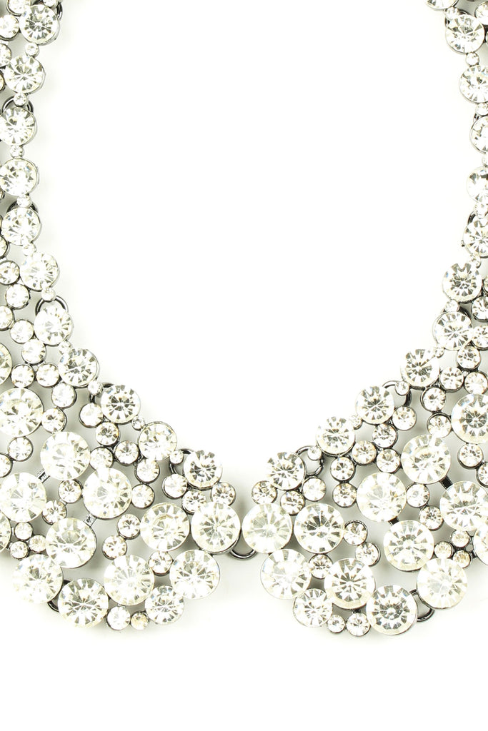 Close up of clear and white crystals set on collar necklace.