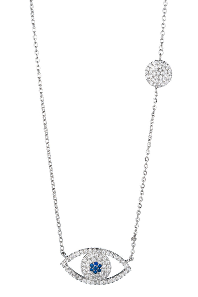 Small silver necklace with thin chain featuring silhouette evil eye pendant with blue iris. Pendant studded with shining cubic zirconia crystals. Small circle charm with cubic zirconia studs also on neckline.