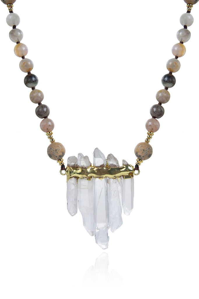 Close up view of pendant on grey agate beaded necklace. Pendant is composed of 5 quartz crystals in pyramid arrangement with gold band wrapped along top. Agate beads made of a variety of grey and brown colors compose the chain.