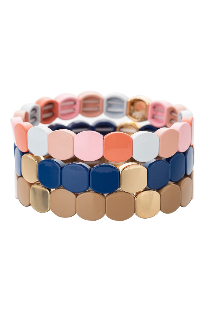 3 piece bracelet set all with rounded square enamel beads. First bracelet features pink and white beads. Second bracelet features navy blue and gold beads. Third bracelet features gold toned beads. All bracelets are stretchy.