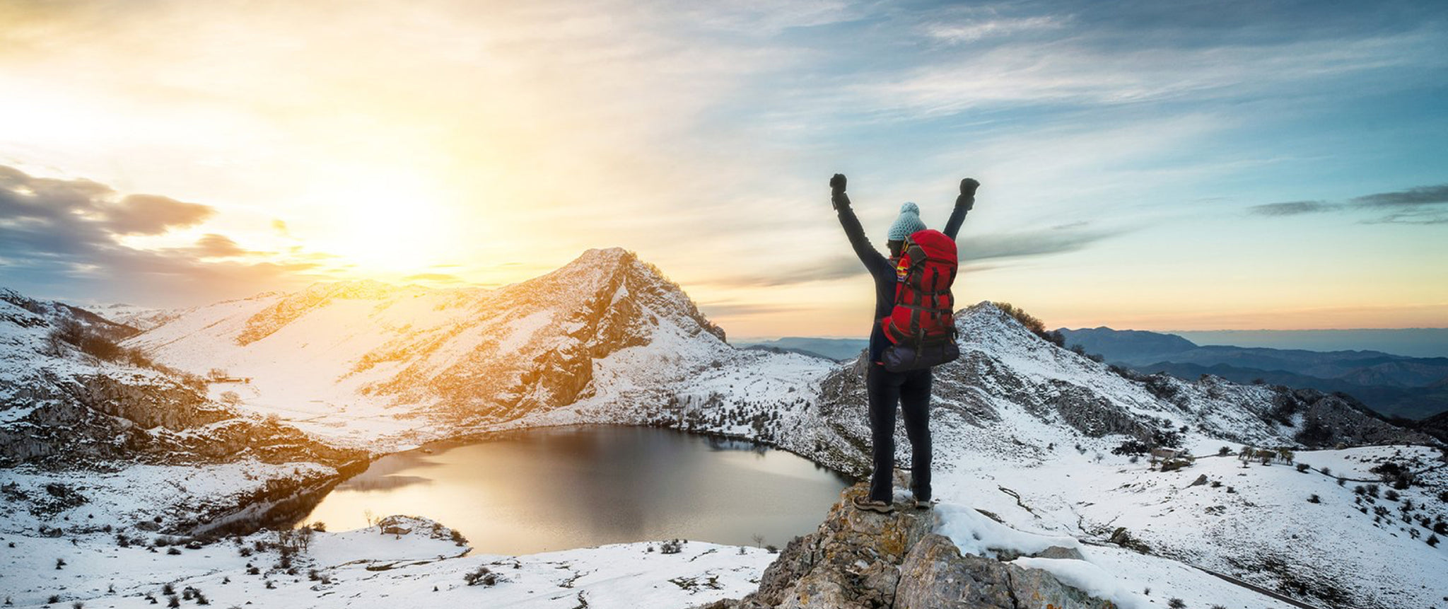 Hiker standing at the edge of a mountain ridge with their hands in the air. They are overlooking snowy mountains and a body of water at sunset